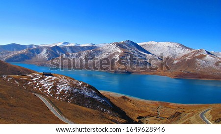 Yamdrok Lake is a freshwater lake in Tibet, it is one of the three largest sacred lakes in Tibet. It is over 72 km long. The lake is surrounded by many snow-capped mounta                            #1649628946