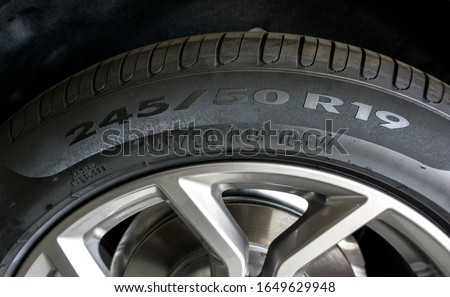 Close up of Number code on sidewall of car tyre with alloy wheel, Tyre Sidewall Markings. #1649629948