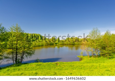 The lake is a large body of water surrounded by land. Walnut and pine trees grow along the edge, complete calm, beautiful hatching in the water #1649636602