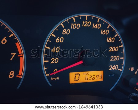 Orange colored light dashboard of stop car with 63693 kilometers odometer and 0 km per hour speed. Royalty-Free Stock Photo #1649641033