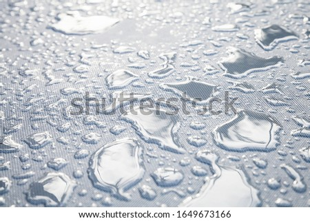 Water drops are on a white plastic fabric. Close-up photo with selective focus #1649673166