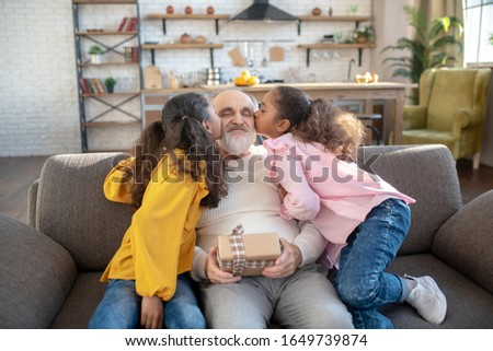 Happy birthday. Two dark-skinned sisters kissing their grandad and giving hime bday gift