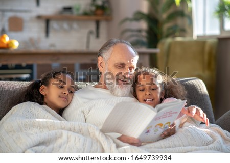 Bedtime stories. Grey-haired granddad reading bedtime stories to his granddaughters #1649739934