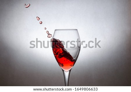 Glass with splashes, drops of red wine on a white background. Freezing liquids in motion #1649806633