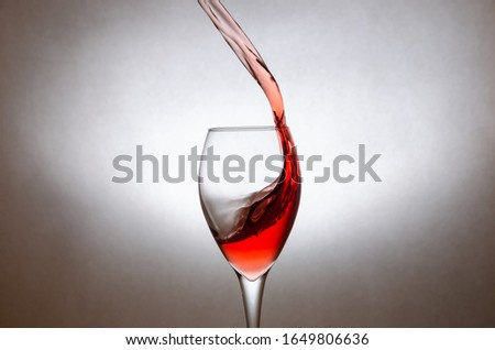 glass of red wine on a white background. Freezing the movement of liquids in the photo. #1649806636