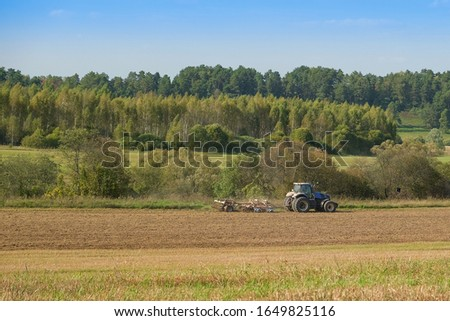 A farm tractor cultivates land after harvesting grain.  #1649825116