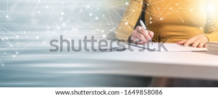 Businesswoman signing document in office; panoramic banner