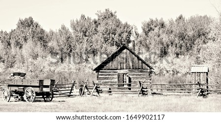 Black and white picture of an old homestead in Colorado showing a cabin, wagon and outhouse.