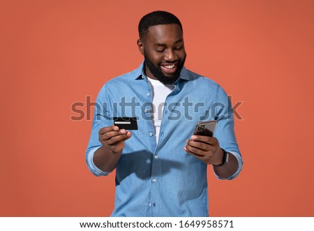 Handsome man makes a payment, using a credit card and smartphone. Photo of african man in casual outfit on coral background.