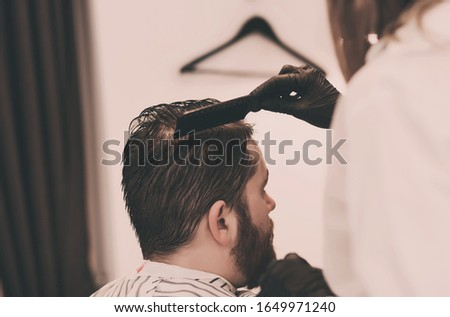 master combs the hair and beards of men in the Barber shop, the Barber makes a hairstyle for a bearded man #1649971240