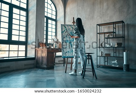 Beautiful asian female painter in art studio. Young talanted artist working.