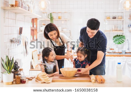 Asian family enjoy playing and cooking food in kitchen at home Royalty-Free Stock Photo #1650038158