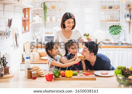 Asian family enjoy playing and cooking food in kitchen at home #1650038161