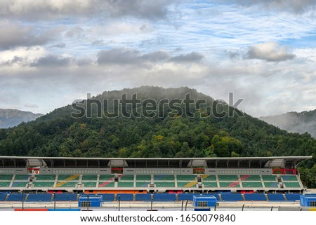 Stadium seats in the racetrack with foggy on mountain  #1650079840