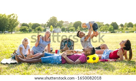 Young multiracial families having fun playing with kids at pic nic garden party - Multiethnic joy and love concept with mixed race people together with children at park barbecue - Warm bright filter