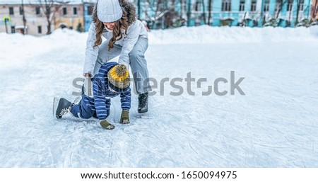 Young mother woman raises son boy 4-5 years ice in winter in city park. The concept of first lesson on skating support and support, help of parents learning sports activities and active lifestyle. #1650094975
