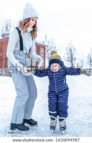 Young mother holds hand of son for boy for 4-5 years, ice skating rink winter in city park. Concept first lesson skating support and support, help parents learning sports activities active lifestyle. #1650094987