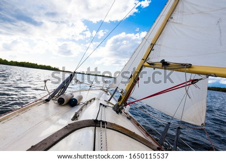 White yacht sailing on a clear day. A view from the deck to the bow and sails. Waves and water splashes. Baltic sea, Latvia #1650115537