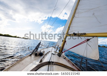 White yacht sailing on a clear day. A view from the deck to the bow and sails. Waves and water splashes. Baltic sea, Latvia #1650115540