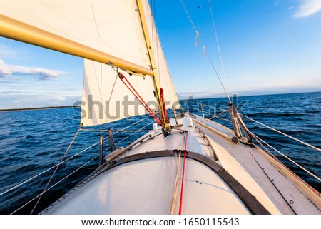 White yacht sailing at sunset. A view from the deck to the bow and sails. Waves and water splashes. Baltic sea, Latvia #1650115543