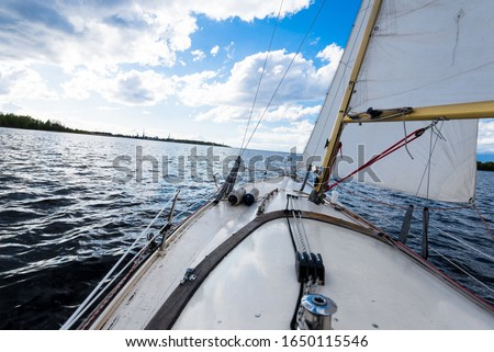 White yacht sailing on a clear day. A view from the deck to the bow and sails. Waves and water splashes. Baltic sea, Latvia #1650115546