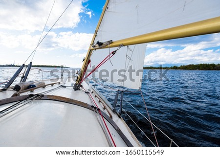 White yacht sailing on a clear day. A view from the deck to the bow and sails. Waves and water splashes. Baltic sea, Latvia #1650115549
