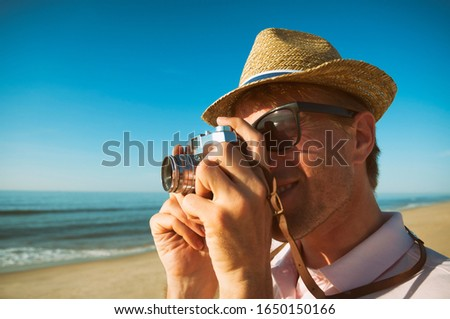 Preppy photographer with straw sun hat taking a picture with a vintage point and shoot camera on an empty beach