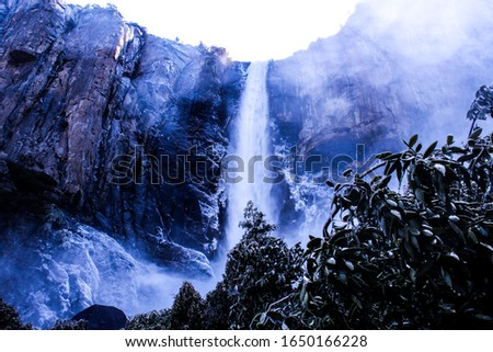 A stunning picture of a Yosemite waterfall. Water streaming down the mountainside in a perfect purple lightning.