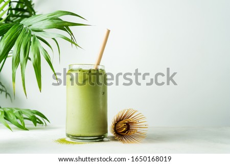 Making Japanese iced matcha latte, green tea with milk, soy milk, traditional matcha tools, with bamboo straw in glass on white background. #1650168019