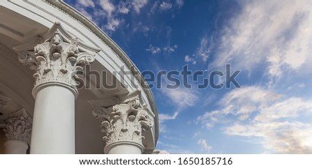 White capitals of columns against the sky #1650185716
