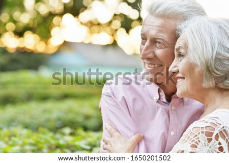 Close up portrait of smiling senior couple embracing in autumn park #1650201502