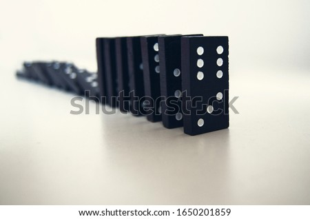 Black Domino on white background, drop, Domino effect, Hobbies, game and entertainment. Falling dominoes selective focus.  #1650201859