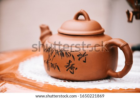 Chinese brown teapot and teacups on the wooden trivet isolated on white Royalty-Free Stock Photo #1650221869