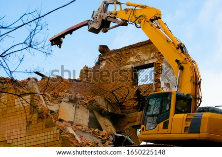 A bulldozer destroys an old building. The concept of the demolition of a building under construction of a new house. Dismantling an old house Royalty-Free Stock Photo #1650225148
