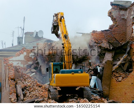 A bulldozer destroys an old building. The concept of the demolition of a building under construction of a new house. Dismantling an old house Royalty-Free Stock Photo #1650225154