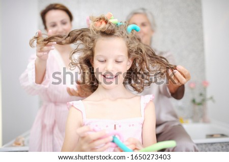 Women styling girl's hair together #1650273403