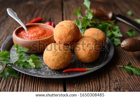 Homemade classic Arancini Di Riso, crispy Sicilian rice balls stuffed with Mozzarella cheese, served with hot Arrabbiata dipping sauce on rustic wooden background #1650308485