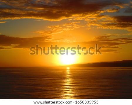 Sunrise with reddish sky on reddish ocean #1650335953