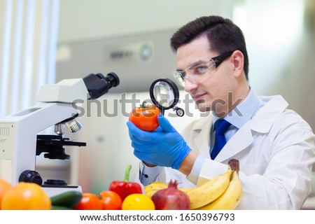 Laboratory worker examining fruits and vegetables and making analysis for pesticides and nitrates. #1650396793