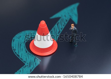 Obstacle, solution idea for business problem or blocker to success concept, miniature people businessman thinking with chalk drawing arrow turn pass the road block traffic pylon on dark blackboard. #1650408784