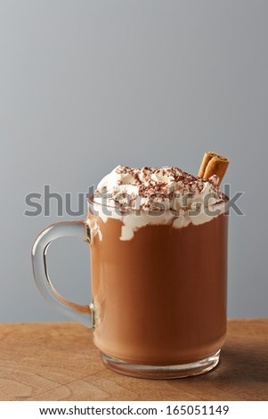 Cup of hot chocolate with whipped cream on wooden table #165051149