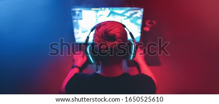 Background professional gamer playing tournaments online games computer with headphones, red and blue.