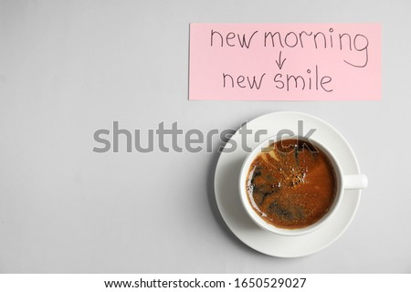 Delicious coffee and card with text NEW MORNING NEW SMILE on light grey background, flat lay. Space for text