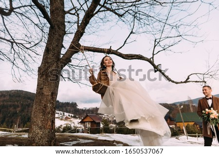 a cheerful and cheerful bride sways on a swing, laughs merrily and enjoys life. Stylish couple in love. #1650537067