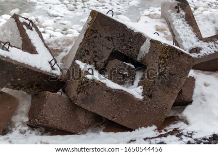 Bank protection - concrete breakwaters on the shore of Lake Ladoga on a cloudy winter day #1650544456