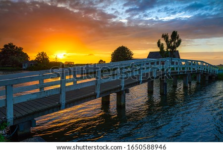 Sunset river bridge in rural scene. Wooden bridge river sunset. Sunset river bridge view. Sunset rural river bridge #1650588946