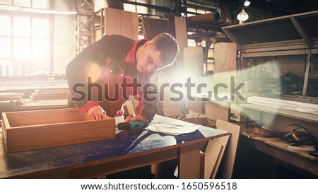 Process of production and manufacture of wooden furniture in furniture factory. Worker carpenter man in overalls processes wood on special equipment #1650596518