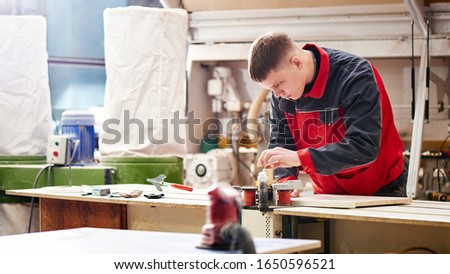 Process of production and manufacture of wooden furniture in furniture factory. Worker carpenter man in overalls processes wood on special equipment #1650596521