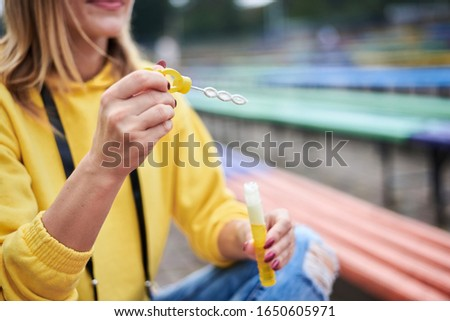 Close-up picture of hands with soap bubbles in process of making them. Young blond woman, wearing yellow hoody, blue jeans and eyeglasses, sitting on colorful bench in city urban park in summer.