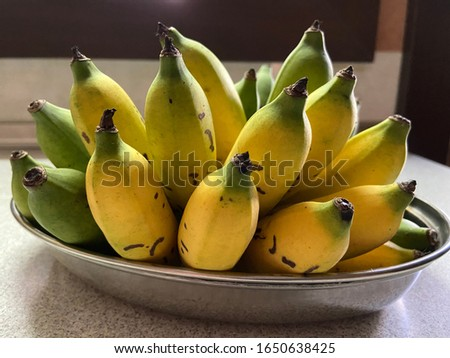 Ripe and partially ripe banana on a plate ready to be served. #1650638425
